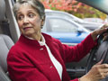 AARP volunteers help teach driver safety programs for members- a car driving speedily around a curve on a road
